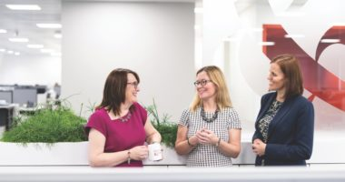 Three female employees chatting in the Mercer & Hole office
